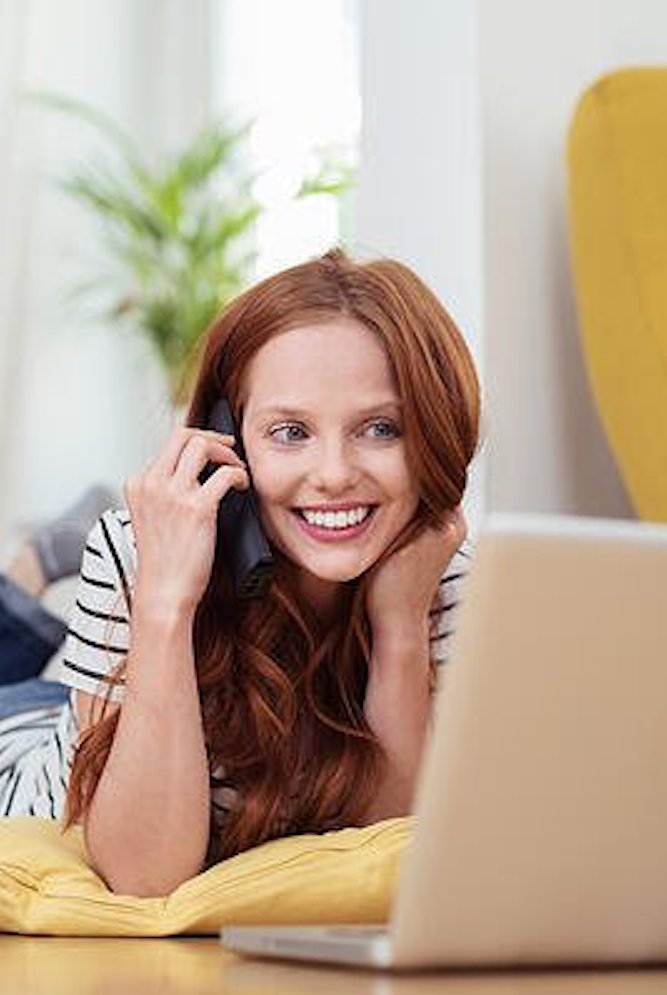 Attractive Young Woman Talking to Someone on Mobile Phone While Relaxing at the Living Room with Laptop Computer-1-2